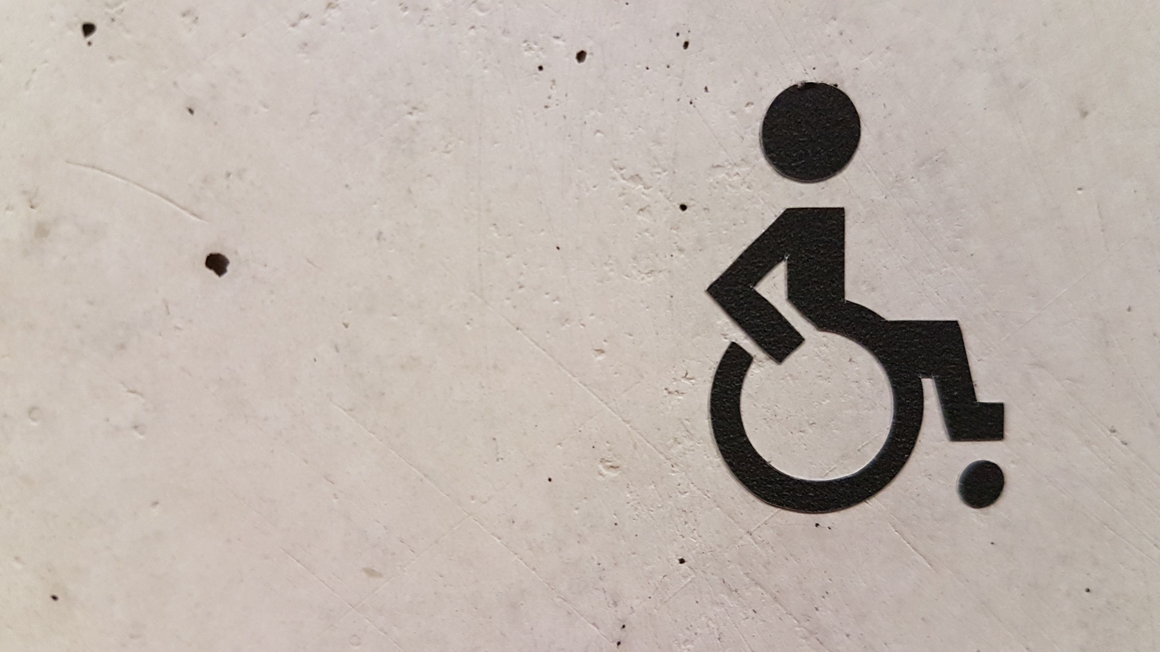 Pictogramme d'une personne en fauteuil roulant sur un mur